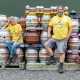Man and woman smiling next to barrels of alcohol